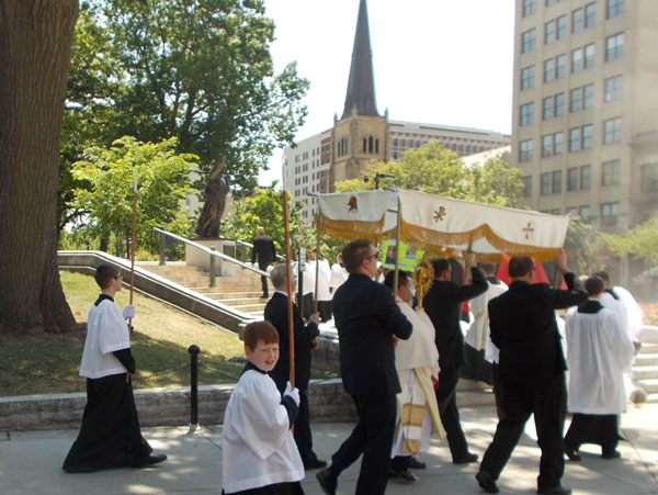 "2012 Madison Corpus Christi Procession approaches the State Street Steps of the Capitol, precisely where the ""Recall Walker"" protests had been centered. In the background, the steeple of Grace Episcopal Church."