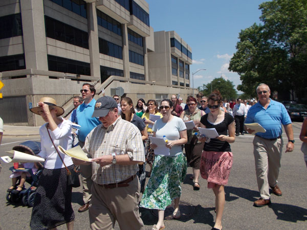 A shot of the people walking in the Corpus Christi Procession toward Capitol Square.