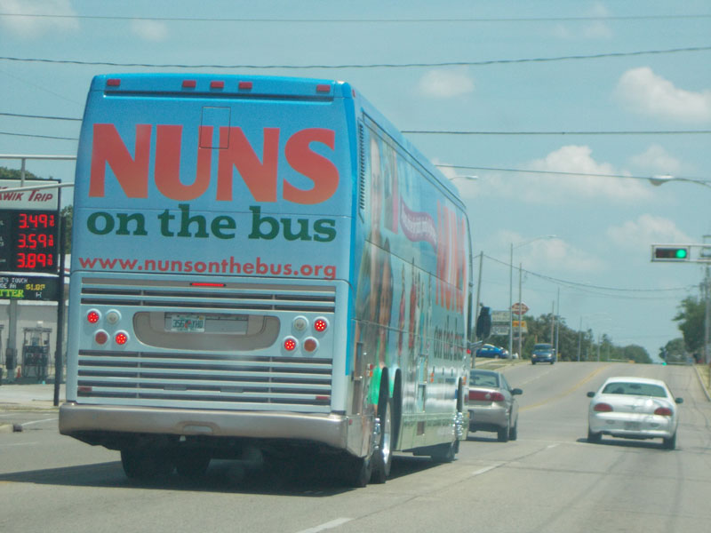 Nuns on the Bus stopped at a red light.