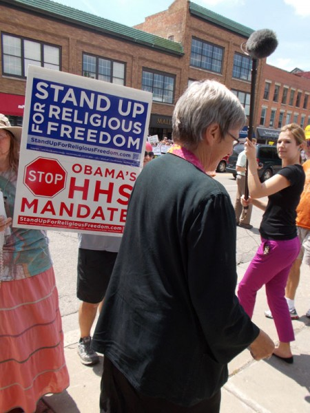"In Janesville, WI, Sister Simone Campbell, Executive Director of NETWORK and head ""nun on the bus"", ignores Jeanne's signs begging her to help stop the immoral ""HHS mandate"" of the Affordable Care Act."
