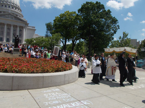 This picture gives an idea of the great crowd of people. There was a convergence of those who attended 11am Mass at St Patrick's, and the 11am Spanish language Mass at Holy Redeemer Church. Now they are preparing to continue to process to Holy Redeemer Church. You can see the chalking on the sidewalk referring to Gov Walker. This was where all the huge Recall demonstrations were.