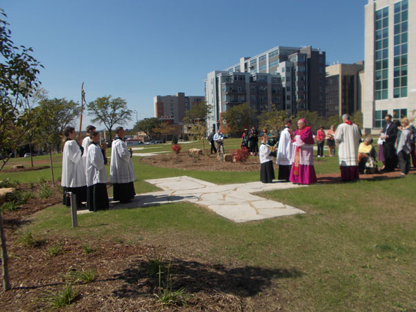 Bishop Morlino blesses the 14th Station, today, September 14th. The large stone blocks you can see scattered here and there among the landscaping are, poignantly, burnt stones from the old Cathedral.