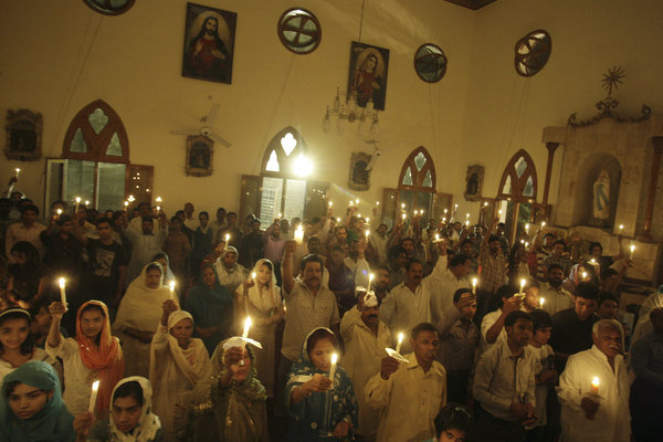 Catholics with candles lit from the Easter Candle at Easter Vigil Mass, Pakistan
